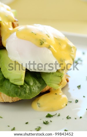 Beautiful eggs benedict with bacon and a rich hollandaise sauce on crusty bread.