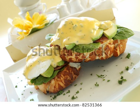 Beautiful eggs benedict with bacon and a rich hollandaise sauce on tiger crust bread.