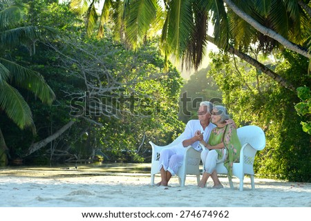 Beautiful  elderly couple sitting on a background of palm trees