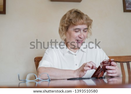 Beautiful elderly woman in a white blouse sitting at the table and writes messages in the phone. Retired woman scored points and reads the message in the smartphone