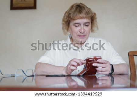 Beautiful elderly woman in a white blouse sitting at the table and writes messages in the phone. Retired woman scored points and reads the message in the smartphone #1394419529