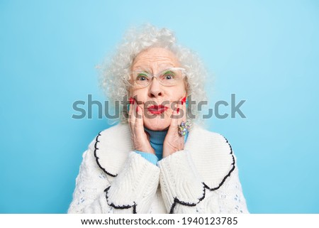 Beautiful elderly woman keeps hands on face folds red painted lips wears spectacles white jumper has well cared complexion isolated over blue background. Retired old female with makeup poses indoor Stockfoto ©