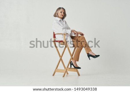 Beautiful elderly woman sits on a fashion chair yes old age retirement