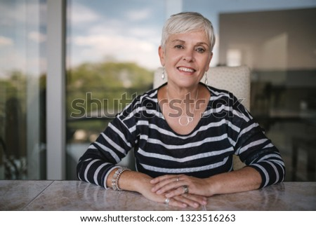Beautiful elderly woman smiling looking into the camera. Portrait of a mature woman with hands crossed on the table, outside on the balcony. Beautiful elderly woman smiling looking into the camera #1323516263