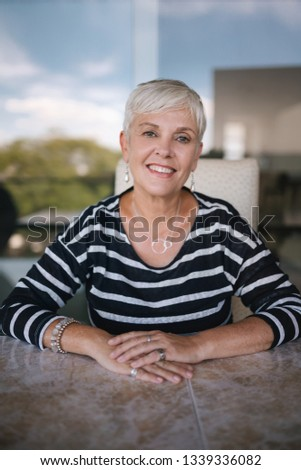 Beautiful elderly woman smiling looking into the camera. Portrait of a mature woman with hands crossed on the table, outside on the balcony. Beautiful elderly woman smiling looking into the camera #1339336082