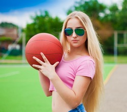 Beautiful elegance girl, has sport athletic slim body, blonde white long hair, clothed in pink t-shirt and blue jeans, sunglasses, hold basketball. Close up. Aviator sunglasses