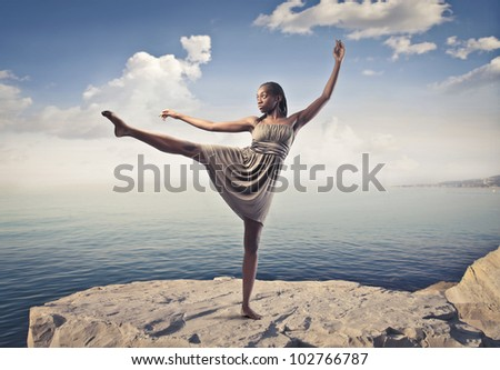 Beautiful elegant african woman dancing on a peak over the sea