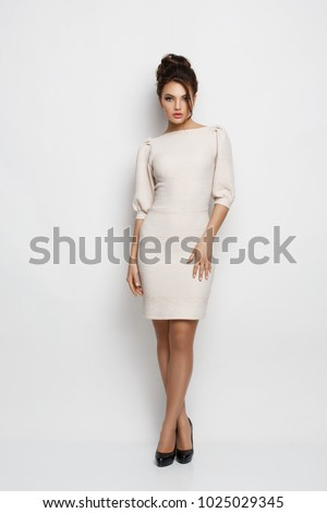 Beautiful elegant, attractive young woman with makeup and hairstyle in the dress and heels is posing in the studio, white background, fashion