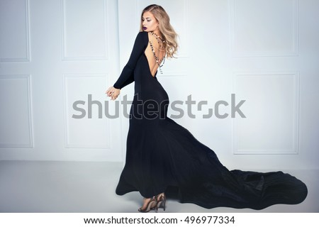 Beautiful elegant blonde woman posing in black maxi dress, back view. Indoor shot.