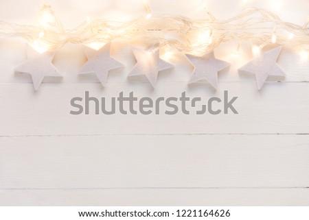 beautiful elegant christmas new year background white stars sparkling golden lights garland on plank wood