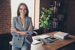 Beautiful elegant classic trendy latin smiling lady freelancer, company founder with folded crossed hands, wearing gray suit, invites to her team, at work place, station, modern fashionable loft