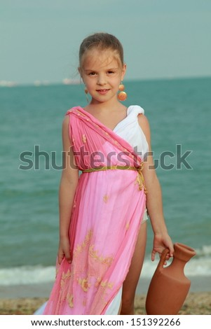 Beautiful elegant girl holding a Greek-style antique amphora and dreams on the beach/Young girl in a role of the Greek goddess of outdoors