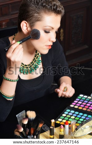 Beautiful elegant lady putting make up at home.