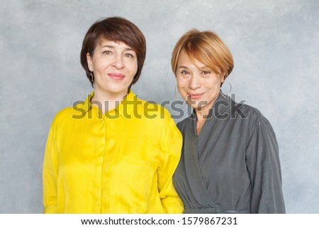 Beautiful elegant mature women smiling and posing on gray background. Two ladies portrait