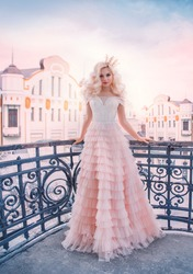 Beautiful elegant princess woman. Queen lady standing on balcony. Backdrop art retro old cityscape blue sky. Long pink medieval vintage dress. Blonde wavy hair volume wig. Royal gold crown cute face