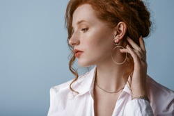 Beautiful elegant redhead freckled woman wearing luxury silver jewelry: earrings, chain, posing in studio, on blue background. Jewellery advertising conception. Close up profile portrait. Copy space