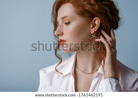 Beautiful elegant redhead freckled woman wearing luxury silver jewelry: earrings, chain, posing in studio, on blue background. Jewellery advertising conception. Close up profile portrait. Copy space Foto stock ©