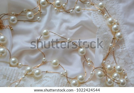 Beautiful elegant romantic elegant background: pearls and golden threads on a white satin (silk) with lace #1022424544