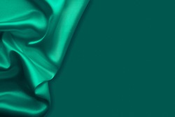 Beautiful elegant wavy emerald green satin silk luxury cloth fabric texture, abstract background design. Card or banner.