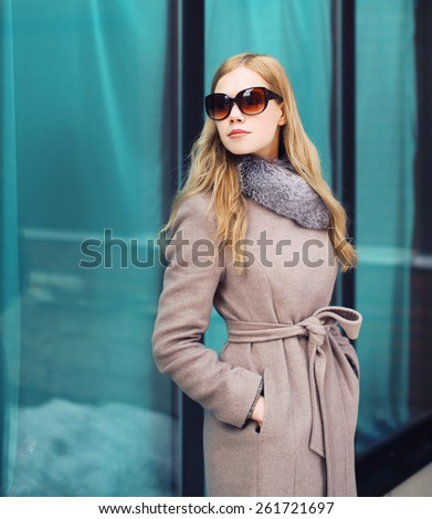 Beautiful elegant woman dressed a coat and sunglasses outdoors in the city
