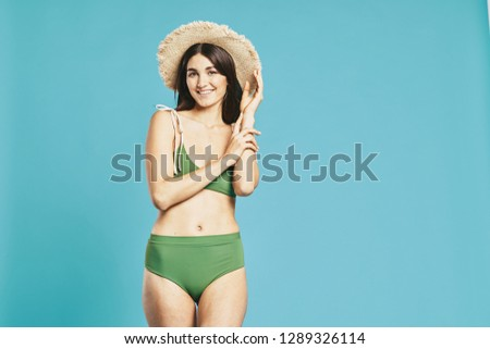 60fcd41005a Beautiful elegant woman in a green bathing suit in a beach straw hat on a  blue