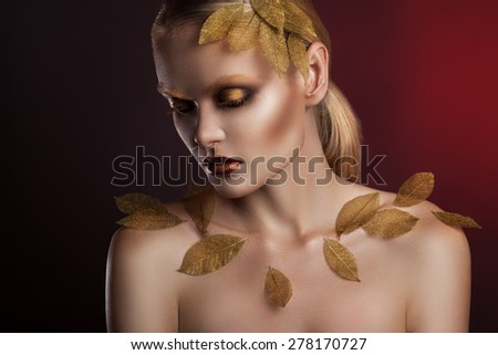beautiful elegant woman in accessories with gold leaves.  portrait