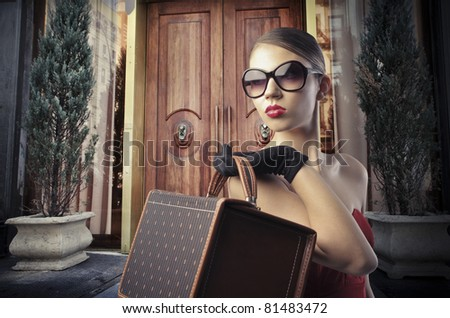 Beautiful elegant woman in front of the entrance door of a luxury building