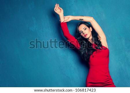 beautiful elegant woman in red dress on blue wall studio shot