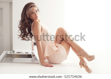 beautiful elegant woman in short pink dress and high heels sit on bar in the modern kitchen