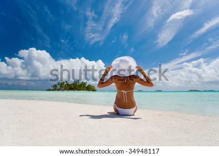 beautiful elegant woman in white on tropical beach