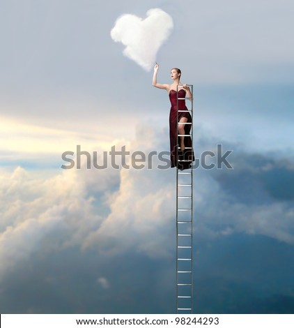 Beautiful elegant woman on a ladder in the sky drawing a heart-shaped cloud