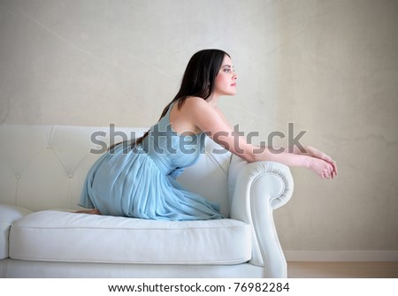 Beautiful elegant woman sitting on a sofa