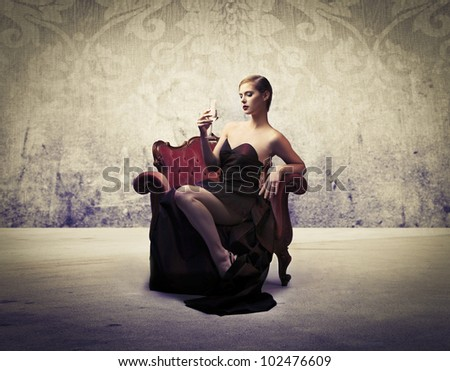 Beautiful elegant woman sitting on an armchair and having a glass of wine
