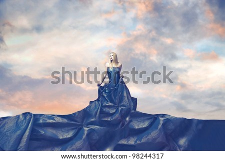 Beautiful elegant woman wearing a very wide evening gown - stock photo