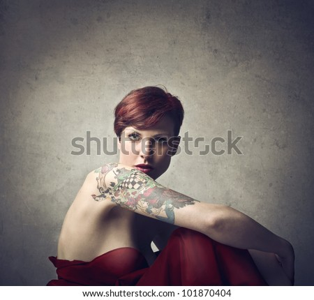 Beautiful elegant woman with a tattoo on her arm