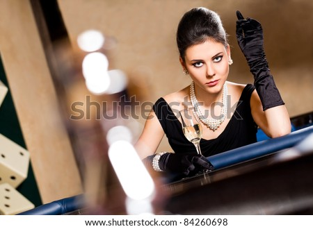 Beautiful elegant woman with black gloves sitting in casino holding a drink