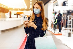 beautiful elegant young woman in a medical protective mask on her face, with shopping bags, uses a mobile phone while in a shopping center