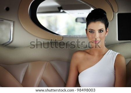 Beautiful elegant young woman sitting in limousine.