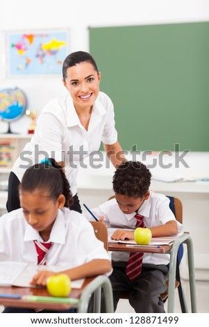 beautiful elementary school teacher in classroom with students