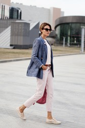 Beautiful emancipated business woman short hair confidently walking street. Determination fashionable woman wears jacket and pants