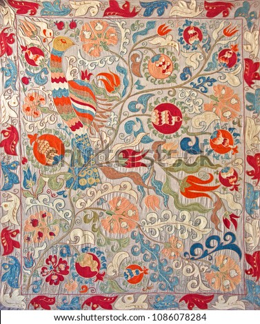 Beautiful embroidery on light grey cotton (ecru) in oriental style. Colorful bird (peacock) on branches of pomegranate tree with abstract floral ornament.