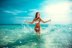 Beautiful emotional Model Girl making splash in the sea and laughing. Beautiful Woman Hot Girl enjoying the Waves of the Ocean. Tropical vacation