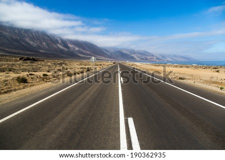 Beautiful empty road in a blue sky day - northern of Chile.