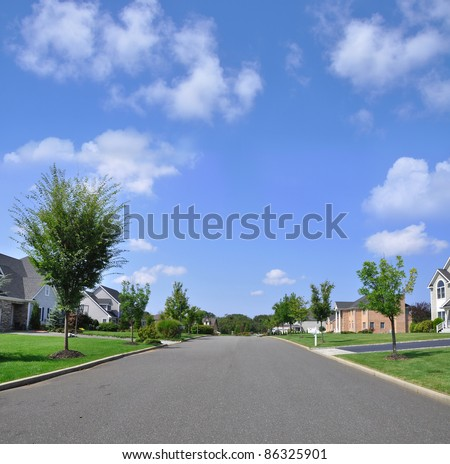 Beautiful Empty Suburban Residential Neighborhood Street on Sunny Blue Sky Day
