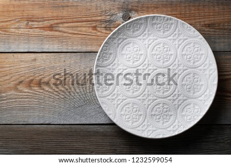 Beautiful empty white plate with ornament on dark wooden table. Top view with copy space. Flat lay #1232599054