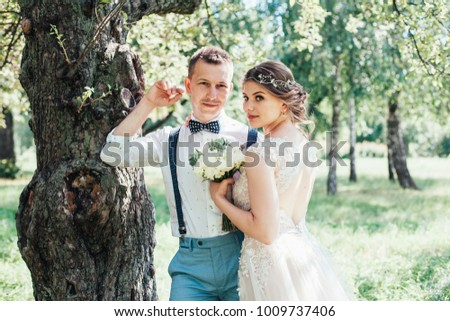 beautiful enamored couple - bride and groom on wedding day in summer #1009737406