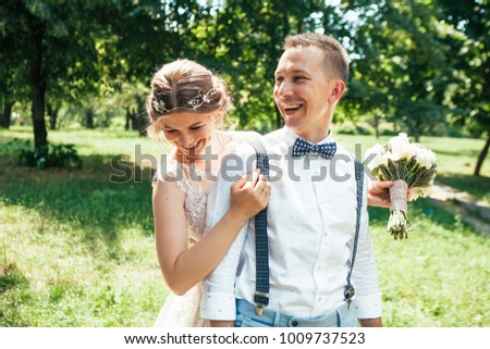 beautiful enamored couple - bride and groom on wedding day in summer #1009737523