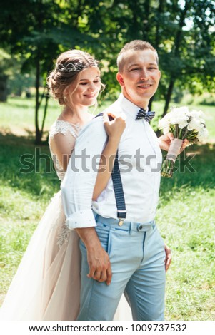 beautiful enamored couple - bride and groom on wedding day in summer #1009737532