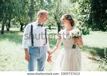 beautiful enamored couple - bride and groom on wedding day in summer #1009737613