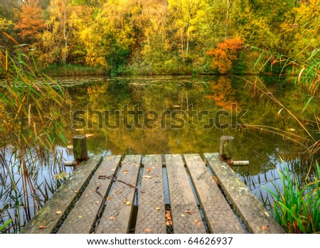 Beautiful English countryside Autumn Fall landscape of fishing jeet on lake with reflections